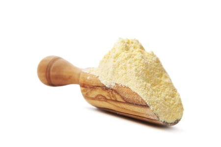 Corn flour poured from wooden scoop