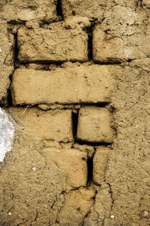Cracked wall made up of mud-brick and soil photo