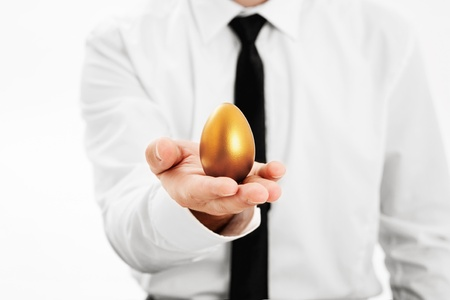 acquire: Businessman holding a golden egg Stock Photo