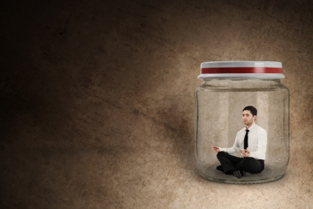 Businessman meditating in jar photo