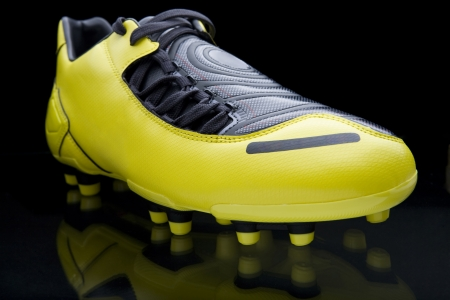 soccer cleats: Yellow soccer footwear on black background Stock Photo