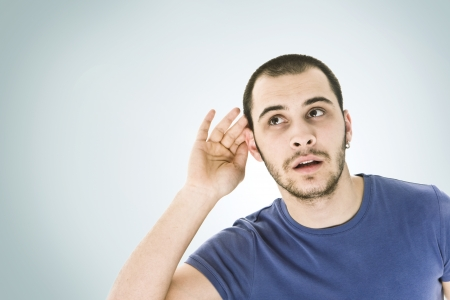 to attend: A young man trying to hearing the sound around him - What did you say