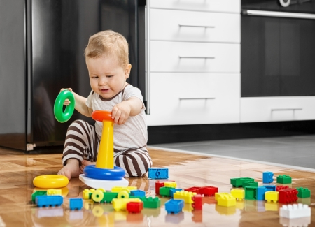 Little boy playing with educational toys on the floor photo