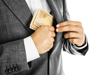 A businessman in a  suit putting money in his pocket
