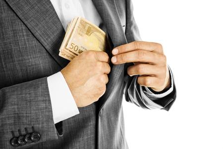 salarios: Un hombre de negocios con un traje a poner dinero en el bolsillo