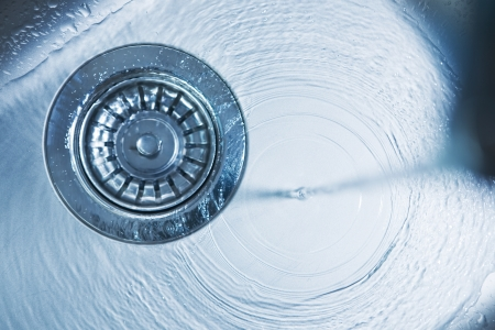 sink drain: Water flowing in a spiral down a stainless steel drain