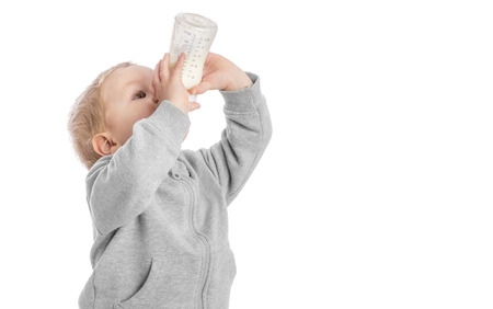 Little boy drinking milk from bottle photo