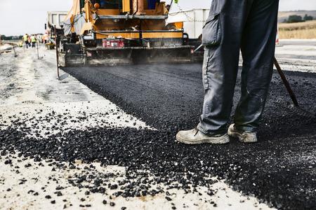 road paving: Trabajador asfalto funcionamiento de la m�quina pavimentadora durante la construcci�n de carreteras y la reparaci�n de las obras
