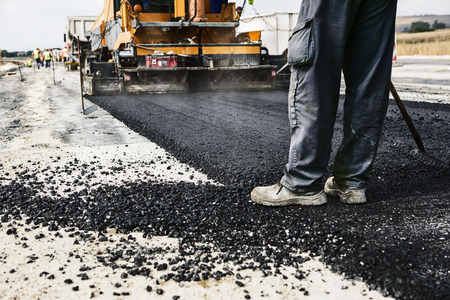Worker operating asphalt paver machine during road construction and repairing works Stock Photo