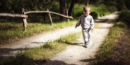 A little boy counts steps on a country road photo