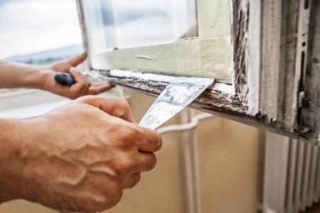Het repareren van een raamkozijn -Man behulp van schraper en stopverf voor renovatie oude ramen