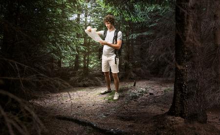 Jonge mannelijke kijken naar de kaart en planning trip of verdwalen in de donkere bossen Stockfoto
