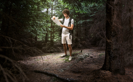 Young male looking at map and planning trip or get lost in the dark woods