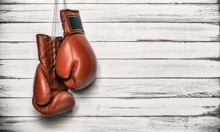 Boxing gloves hanging on wooden wall photo