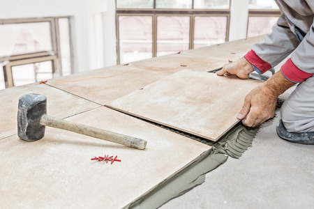 Handyman laying tile, trowel with mortar Standard-Bild