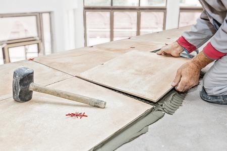 Handyman laying tile, trowel with mortar Stockfoto