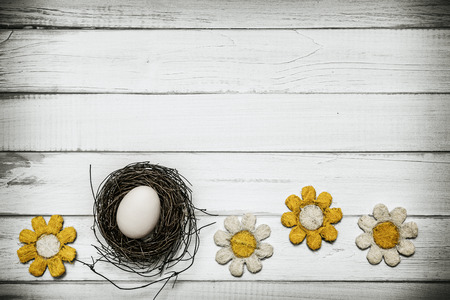 april flowers: Egg in nest with flowers around on wooden background -Concept that announces spring and Easter holidays