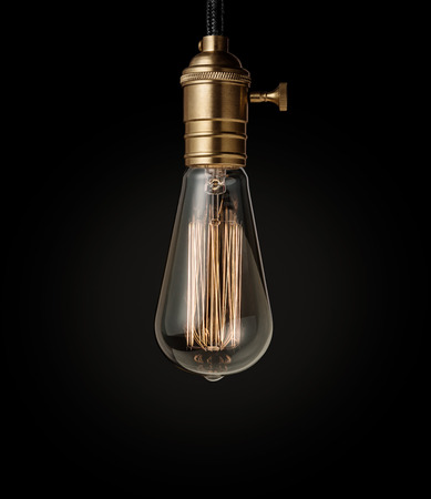 Edison light bulb on black background photo