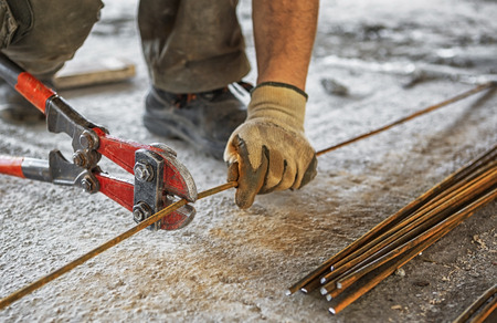 reinforcing bar: Worker cuts steel bars with bolt cutter on construction site