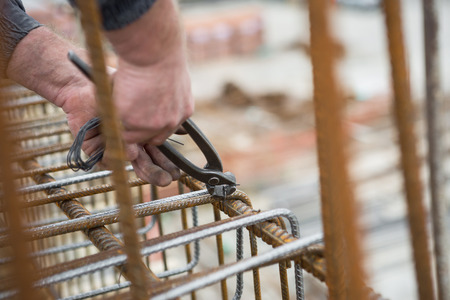 pincers: Worker hands using steel wire and pincers to secure rebar before concrete is poured over it Stock Photo