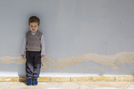 three year old: Portrait of a small boy on the old blue wall
