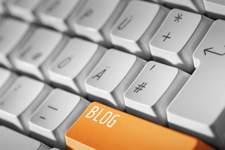 Blog business concept Orange button or key on white keyboard Banque d'images