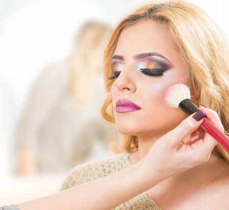 sexy bride: Young beautiful bride applying wedding make-up by make-up artist