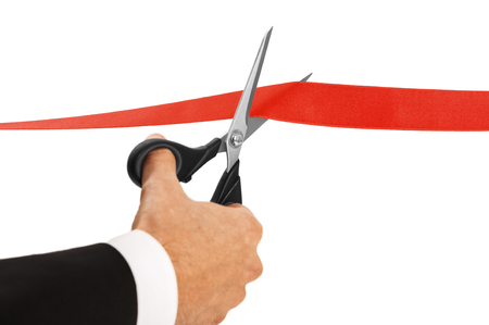 Red ribbon cutting with a pair of scissors for the inauguration of the new business activity
