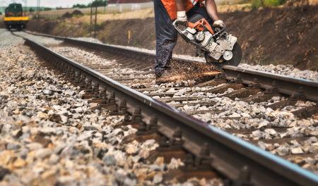 Reconstructie van de spoorweg -Werker op de spoorlijn snijdt spoor met een machine Stockfoto