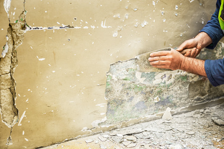 Home renovation -Worker scraping old paint on wall Standard-Bild