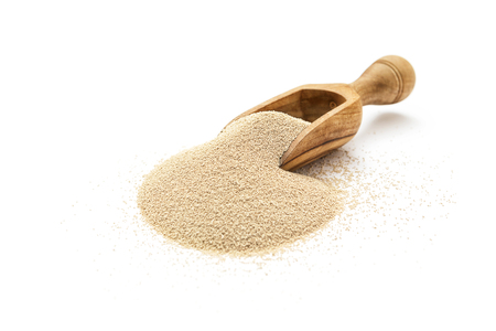Dry yeast in wooden scoop on white background 스톡 콘텐츠