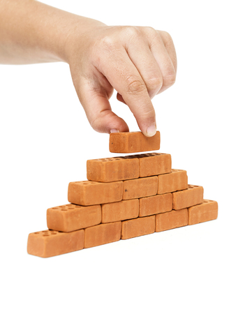 Concept of building and construction, a hand placing a brick on a wall, on a white background Stok Fotoğraf