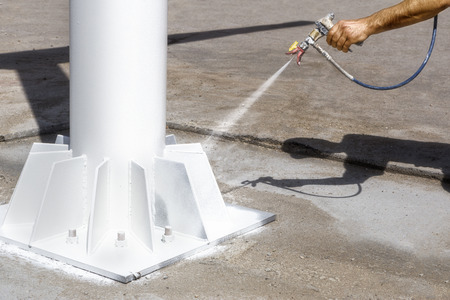 Worker uses an airless spray to paint the metal construction