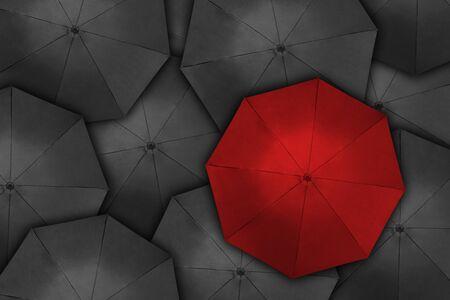 Sich von der Masse abheben, Blick aus der Vogelperspektive auf den roten Regenschirm über vielen dunklen