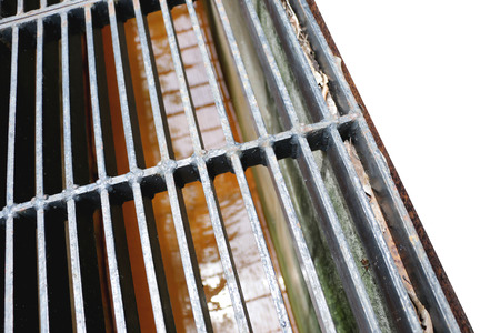 drain water: Middle point focus of steel drain water flows down through the steel manhole cover on a sunlight afternoon. Stock Photo