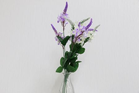 dried flower arrangement: Plastic flowers in a vase on a dark gray background