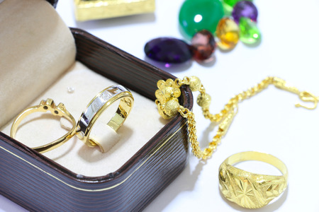 faceting: Precious jewels ,Rings with diamonds and gold, Emeralds and corals on pounds in gem Stock Photo