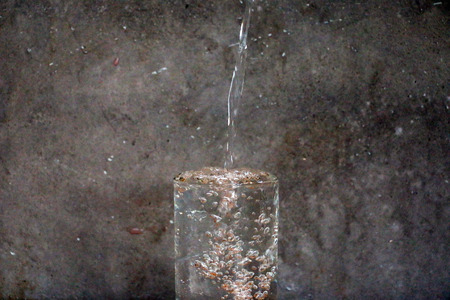 shooter drink: Action of drop water and Water glass on the wood table in front of the cement wall background