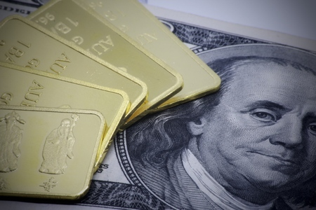 Gold bar ingot close up on the US money dollar background Stock Photo