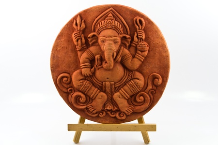 idol: Sphere of clay Ganesh statue on wooden base.