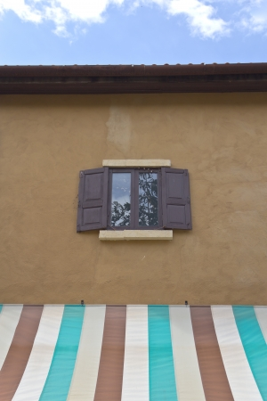 awnings windows: Windows made of wood on the walls and awnings  Stock Photo