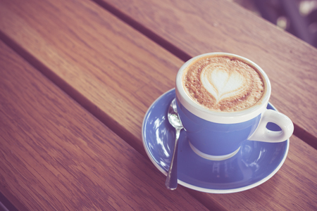 coffee table: Cappuccino on a wooden table.