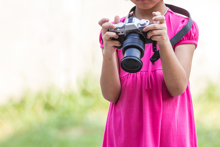 young girl taking photos by mirrorless digital camera.