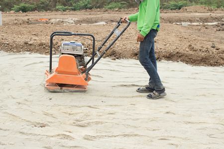 roadwork: worker at sand ground compaction with vibration plate compactor machine before pavement roadwork