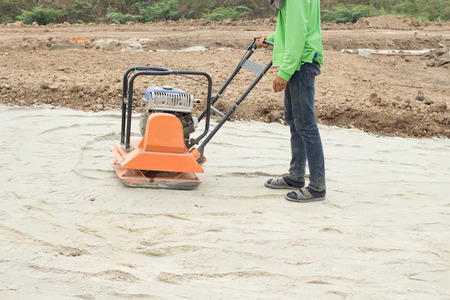 worker at sand ground compaction with vibration plate compactor machine before pavement roadwork