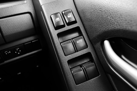 lift lock: Car door interior armrest with window control panel, door lock button, and mirror auto  and manual control with monochrome