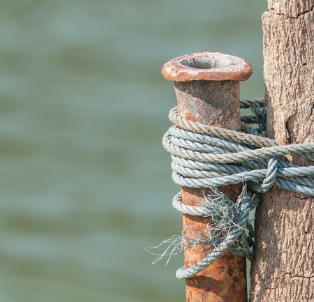 crack pipe: Old rusty pipe tied up to wood by some rope. Stock Photo