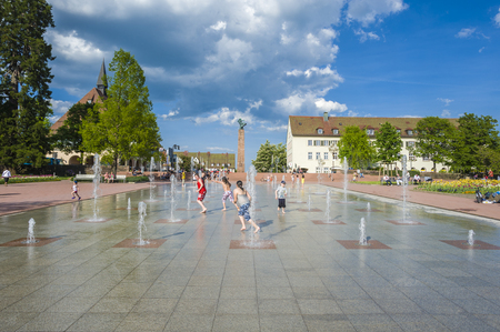 playing the market: Playing children at the lower market place with fountains in Freudenstadt in the Black Forest, Baden-Wurttemberg, Germany, Europe Editorial