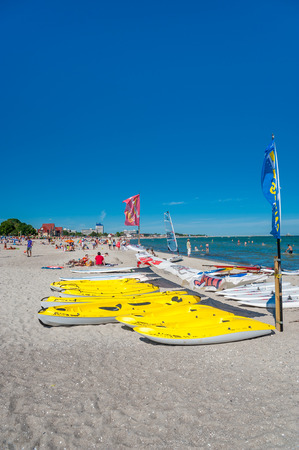 Surfboards, kayaks and tourists on the beach in Groemitz at the Baltic Sea