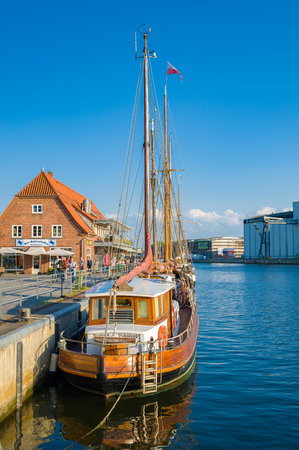 Harbor of Neustadt in Holstein with traditional sailing ships and a restaurant at the quay